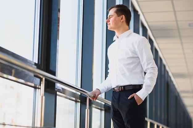 紺色の壁の窓際に立っている白いシャツを着て、窓の外を眺めている青年実業家の横顔を見る。