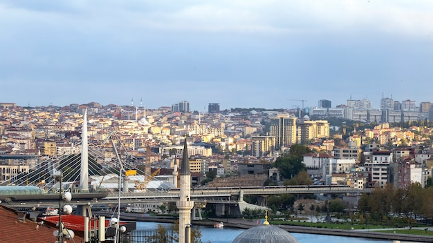 View of the istanbul at cloudy weather, bosphorus strait dividing city into two parts, multiple buildings, bridge, turkey
