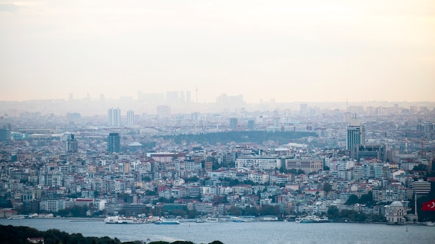 View of the istanbul at cloudy weather, multiple low and high buildings, fog, bosphorus strait on the foreground, turkey