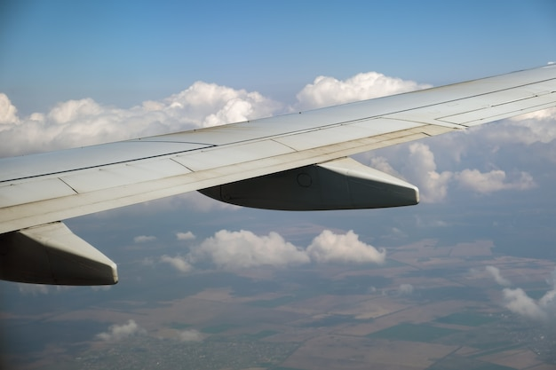 View of jet airplane wing from inside flying over white puffy clouds in blue sky. travel and air transportation concept.