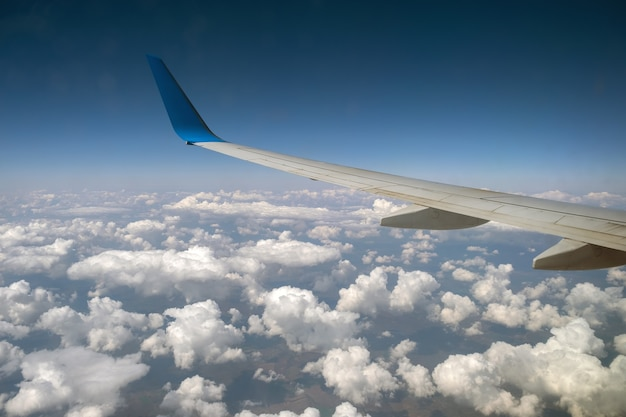 View of jet airplane wing from inside flying over white puffy clouds in blue sky.