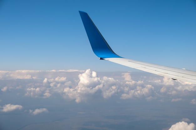 View of jet airplane wing from inside flying over white puffy clouds in blue sky
