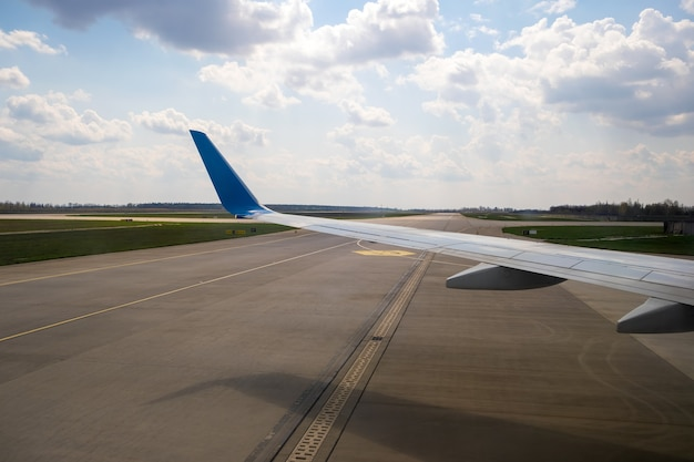 View of jet airplane wing taxiing runway after landing at airport. travel and air transportation concept.
