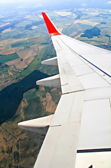 View of jet plane wing during landing above germany