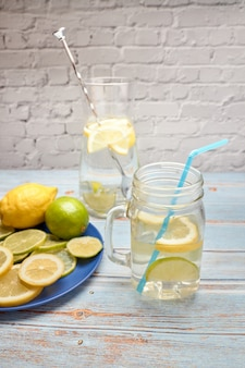 View of a jug of lemonade with ice and lemon