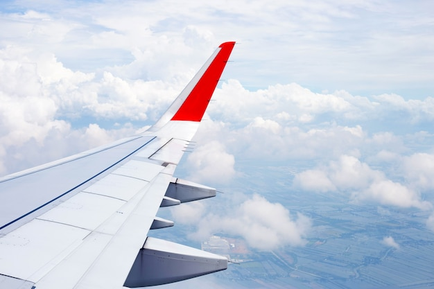 View of land, cloud and wing of airplane from window