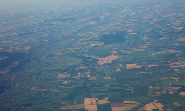 View of the land surface from a window of the plane flying at big height