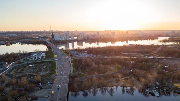 ウクライナの日没のキエフの左側にある、スカイモルショッピングセンターとオボロン地区を見下ろすドニエプル川に架かるノースブリッジの風景をご覧ください。ドローンからの写真