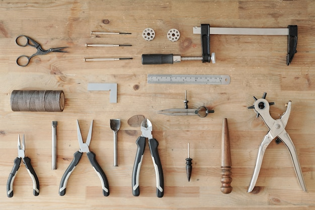 Above view of leather work tool set such as rotary punch, ruler, thread, pliers, edge burnisher on wooden table