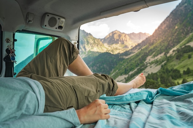 View of the legs of a happy girl inside a minivan at sunset