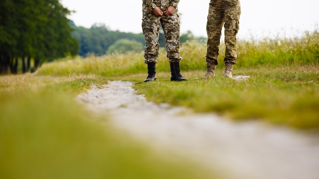 View of the legs of two men in military uniforms in boots near the pathway in the field
