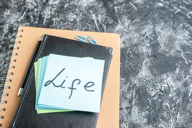 Above view life written note with stickers and copybook on gray surface team color job photo business office work school college notepad