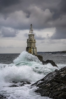 View of lighthouse during stormy weather on a dark sky background