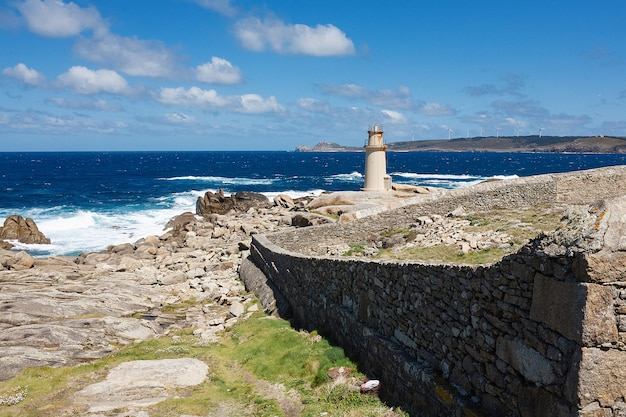 View on a lighthouse near the ocean with blue skies and white clouds