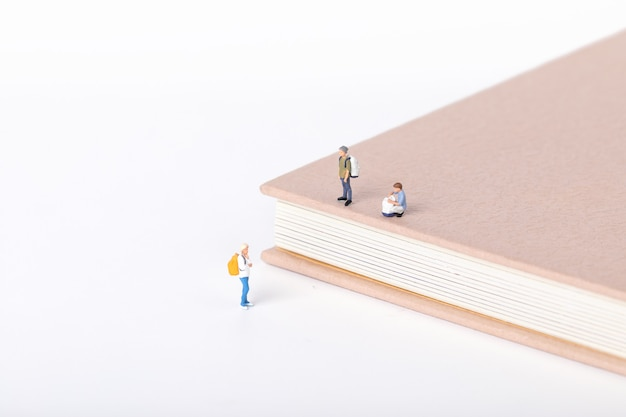 Vista di piccole figurine di studenti in piedi intorno a un libro di testo su bianco