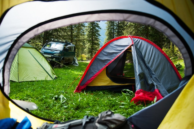 View looking out of door of sun-filled tent upon great outdoors scenery