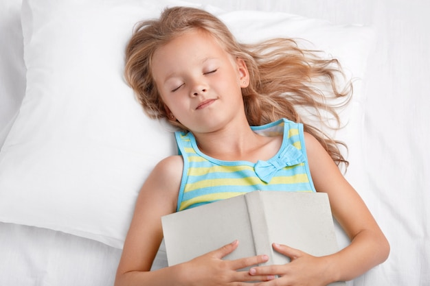 View of lovely girl with long light hair sleeps after reading fairy tale, keeps book on stomach, lies in comfortable white bed, has pleasant dreams, enjoys fairytale. children and relaxation concept