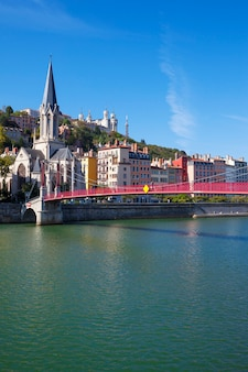View of lyon city with red footbridge on saone river and church