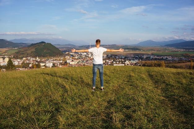 Vista di un maschio in piedi su una collina con le braccia aperte mentre guarda con orgoglio la sua città natale