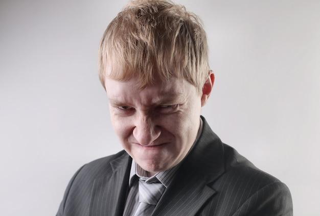 Vista di un maschio che indossa un abito nero con un'espressione facciale arrabbiata