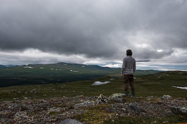 Vista di un uomo in piedi su una collina rocciosa con nuvole tempestose