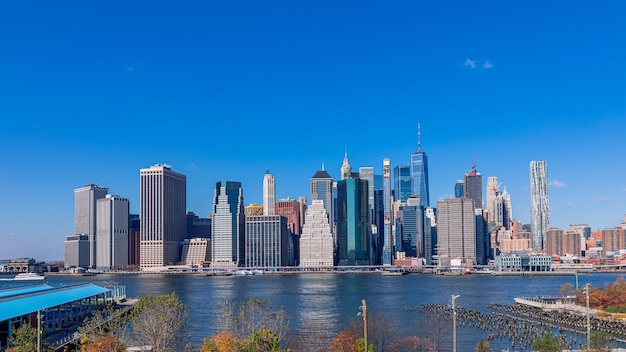View of manhattan island new york city from brooklyn bridge park on a sunny autumn day