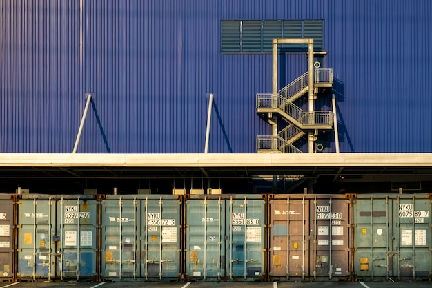 View of many shipping containers doors with fire escape background.