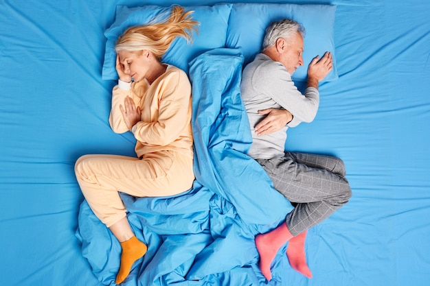 Above view of married old couple sleep deeply lying back to each other in comfortable bed wear soft pajamas have good rest after hard working day enjoy cozy atmosphere. people sleeping concept