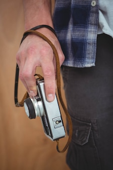 View of masculine hands holding a retro camera