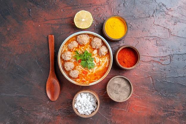 Sopra la vista della zuppa di polpette con noodles in una ciotola marrone cucchiaio di limone e spezie diverse su sfondo scuro