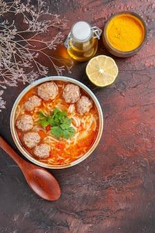 Sopra la vista della zuppa di polpette con le tagliatelle in una ciotola marrone, cucchiaio di limone e bottiglia di olio su un tavolo scuro immagine stock