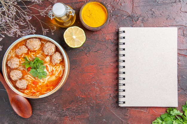 Sopra la vista della zuppa di polpette con noodles in una ciotola marrone, cucchiaio di limone, bottiglia di olio e taccuino sul tavolo scuro
