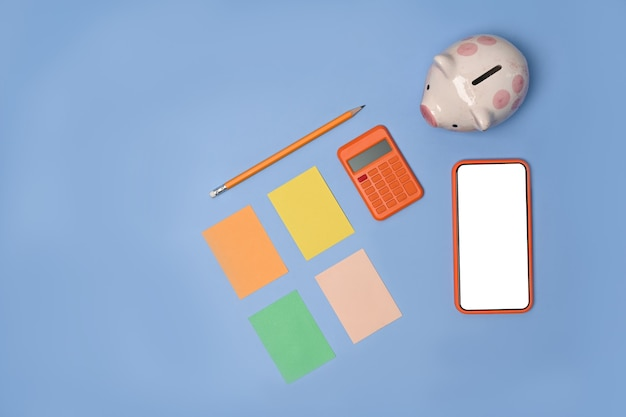 Above view of mobile phone, sticky note, calculator piggy bank on blue background.