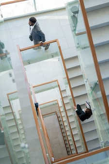 Above view of modern business people moving in stairway of office center while coming to workplace