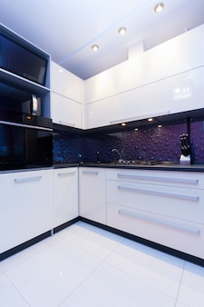 View of modern glossy white and violet kitchen