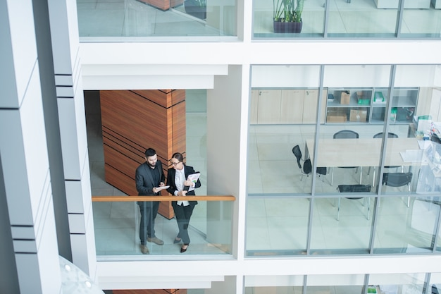 Above view of modern young business analysts standing at glassy railing and discussing report using tablet