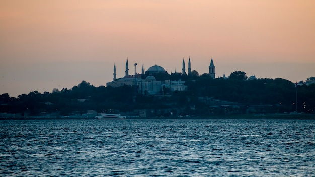 View of a mosque and a lot of greenery around it at evening, bosphorus strait on the foreground in istanbul, turkey