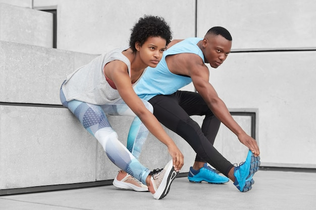 View of motivated teenagers demonstrate good flexibility, lean to feet, do stretching exercises near stairs, wear comfortable sneakers for training, have dark healthy skin, strong muscular body