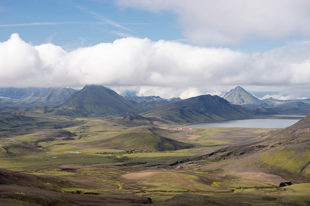 Вид на горную долину с зелеными холмами, речным ручьем и озером. походная тропа лаугавегур, исландия.