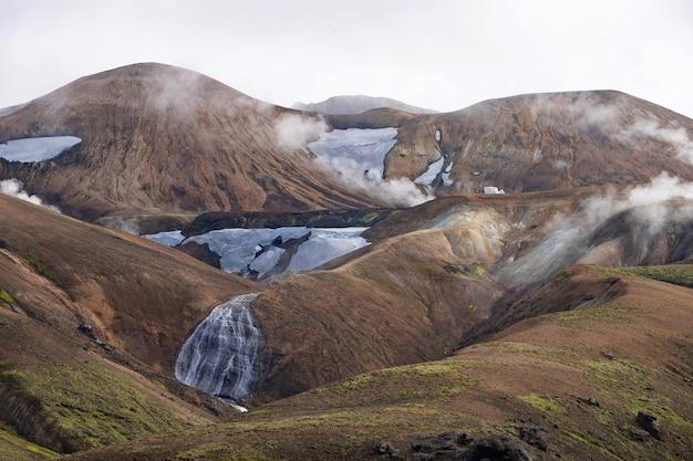 Вид на горную долину со снегом, водопадом, мхом и туманными холмами. походная тропа лаугавегур, исландия.