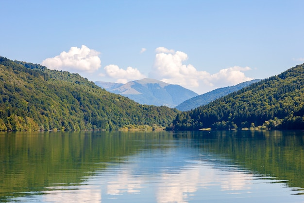 View of mountains in summer with lake in front