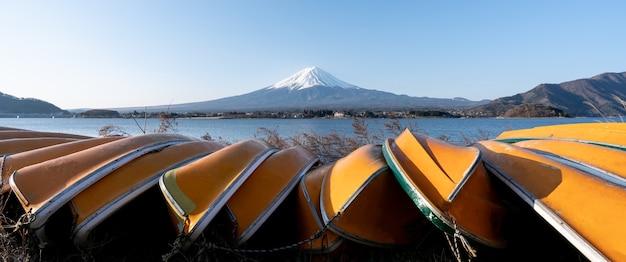 View of mt. fuji or fuji-san with yellow boat and clear sky at lake kawaguchiko, japan.