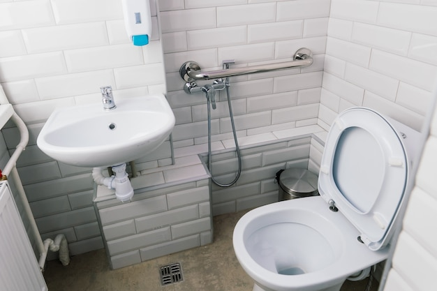 View of a new toilet and bathroom interior for hospital, white and clean