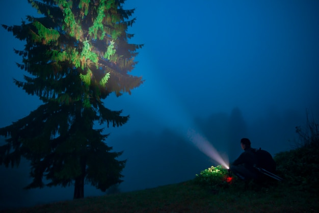 View of night tree, man with a flashlight in foggy mountain valley
