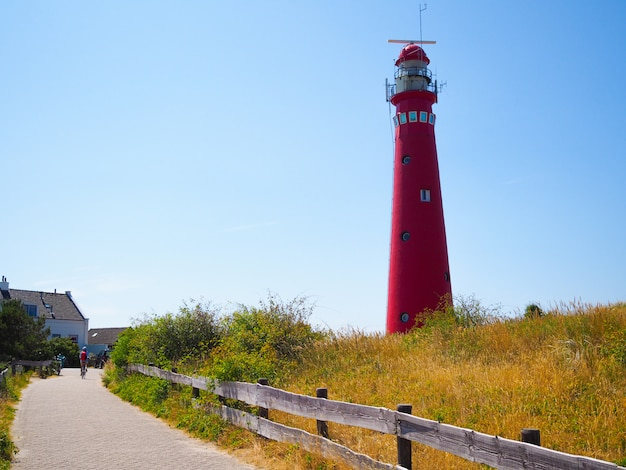 View of the north tower - lighthouse in schiermonnikoog islands one of the frisian islands, on sand dune against blue sky