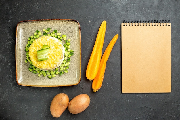 Above view of notebook and delicious salad served with chopped cucumber and carrots with potatoes on dark background