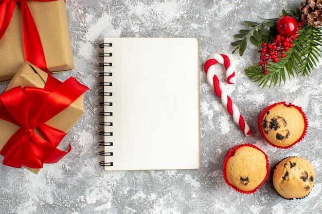 Vista dall'alto di taccuino e piccoli cupcakes, caramelle e rami di abete, accessori per la decorazione e regalo con nastro rosso sulla superficie del ghiaccio ice