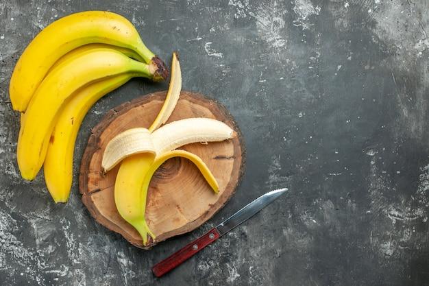 Vista sopra la fonte di nutrizione pacco di banane fresche e sbucciate su tagliere di legno coltello su sfondo grigio