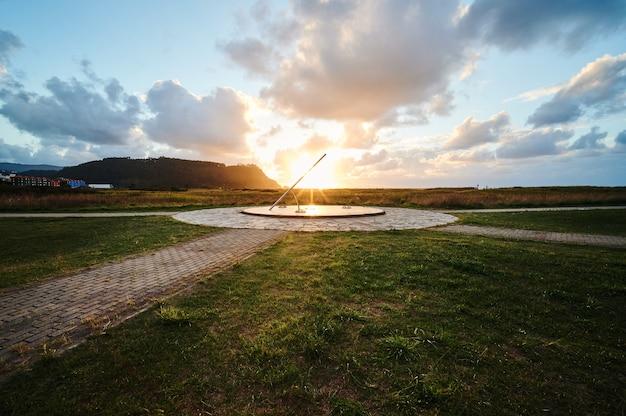 마지막 햇빛 광선에 의해 조명된 해시계가 있는 해안 마을의 아름답고 화창한 일몰의 전망.