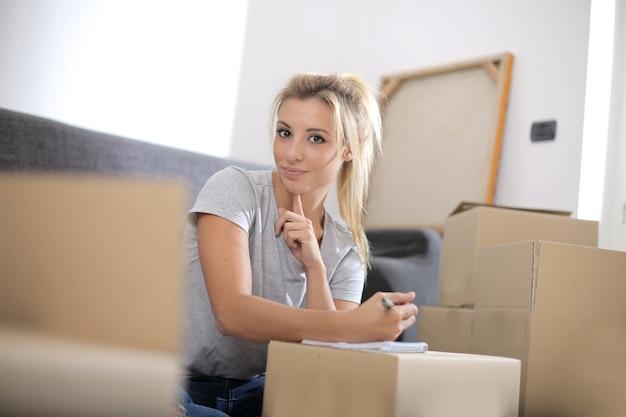 상자에 둘러싸인 노트북에 쓰는 아름다운 백인 여성의보기